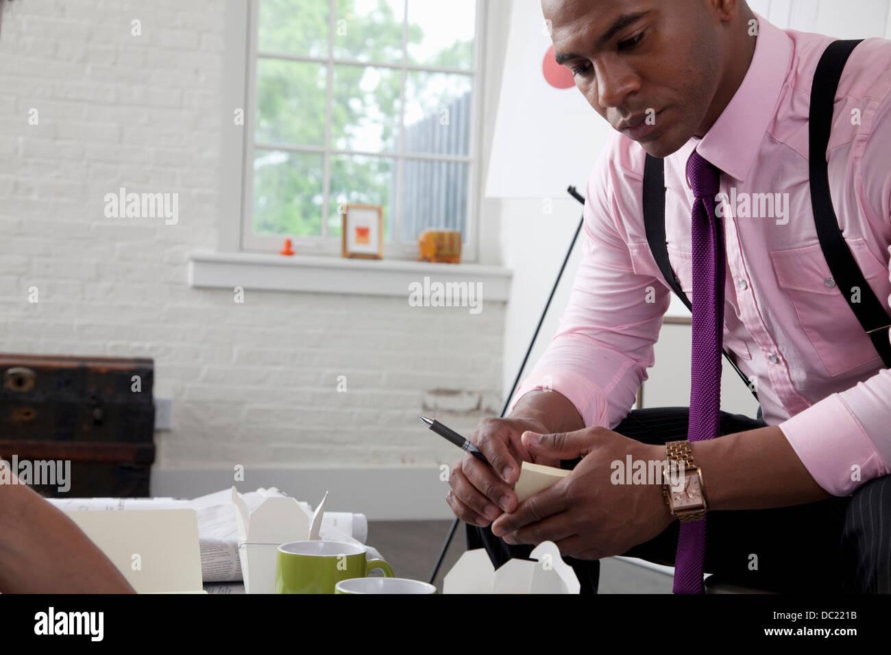 A mediados adulto trabajador de oficina mirando el papeleo en la tabla Imagen De Stock