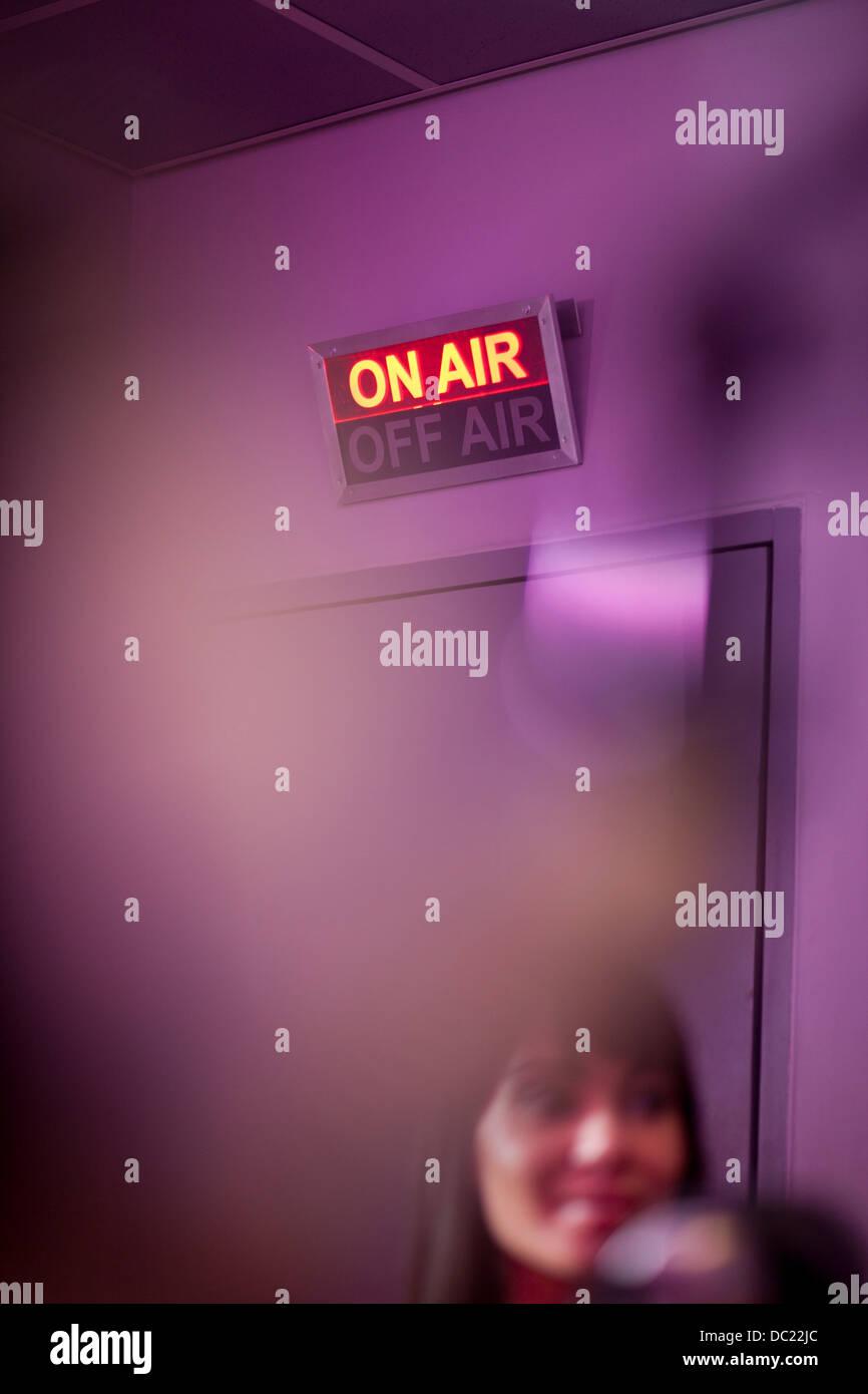 Mujer adulta media en el estudio de grabación con señal luminosa Foto de stock