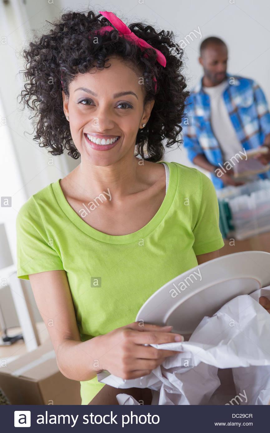 Mujer adulta media desenvolver placa, hombre en segundo plano. Imagen De Stock