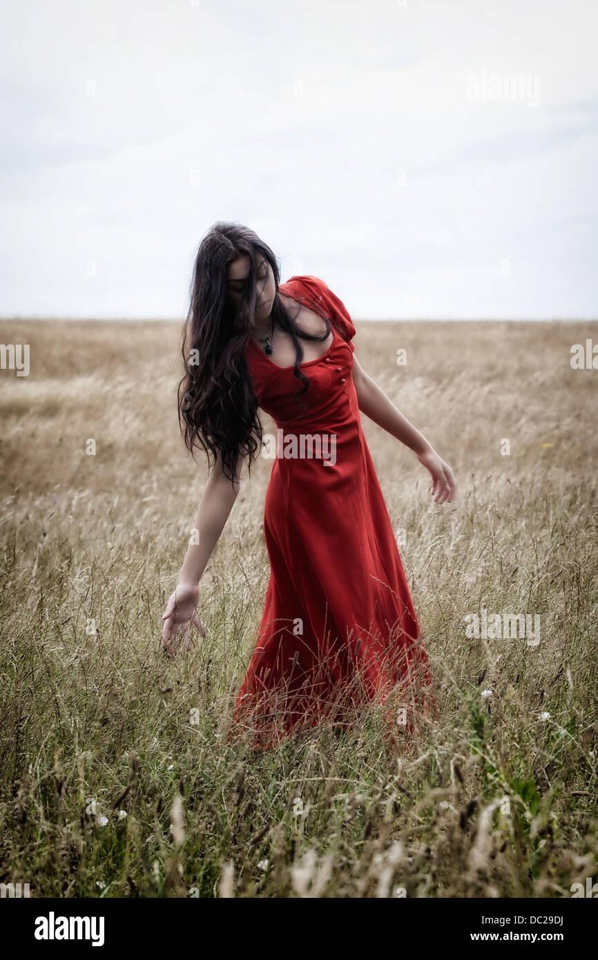 Una mujer en un vestido rojo sobre un campo, jugando con el grano Imagen De Stock