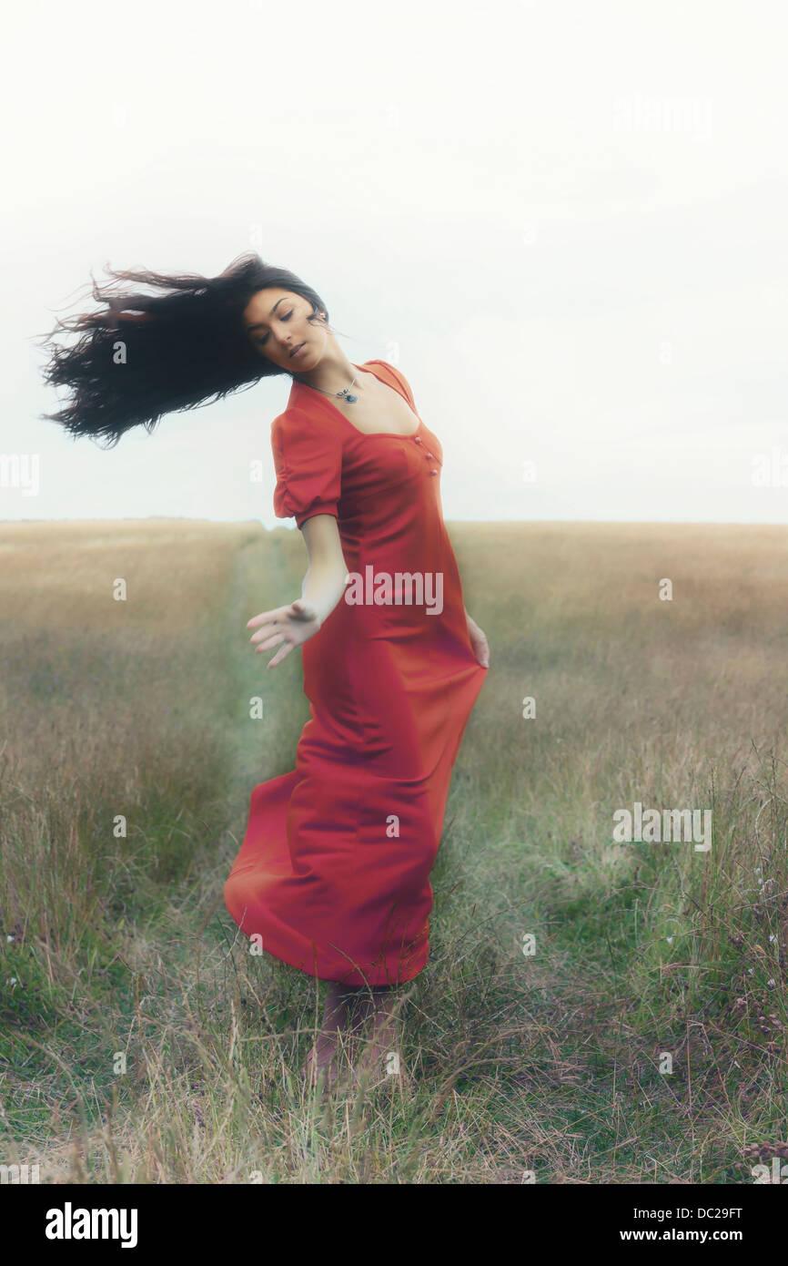 Una mujer en un vestido rojo está bailando en un campo Imagen De Stock
