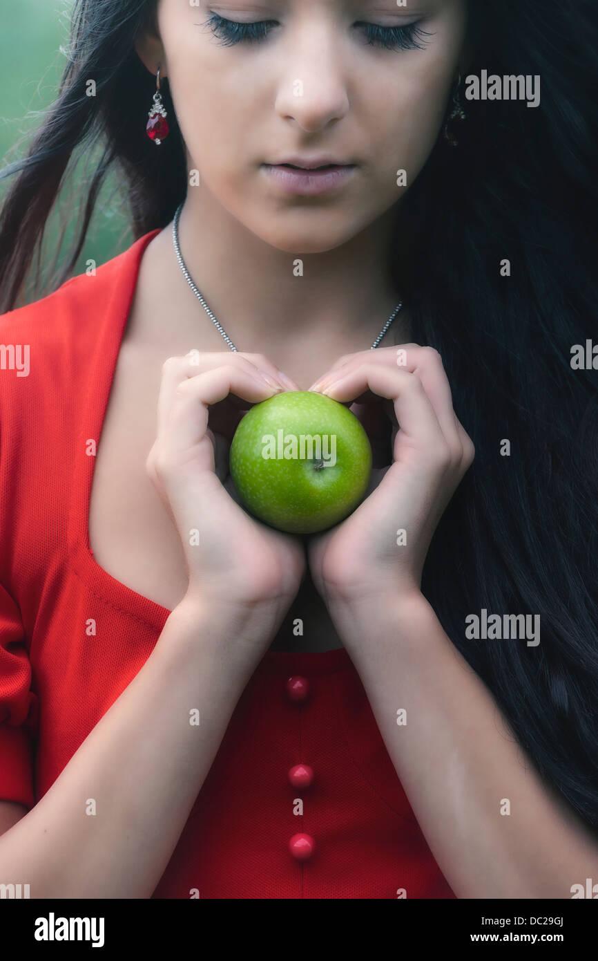 Una mujer en un vestido rojo, sosteniendo una manzana verde Imagen De Stock