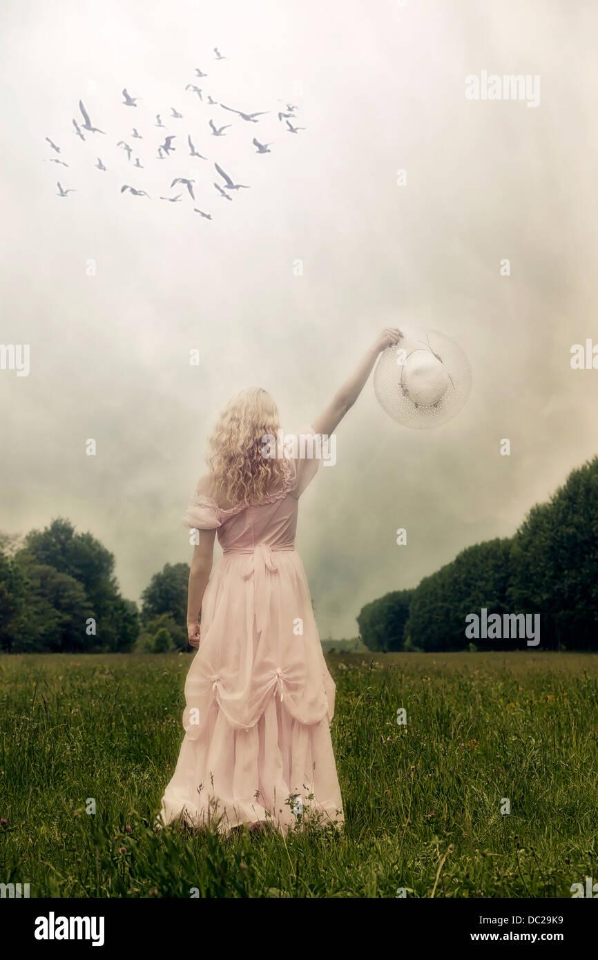 Una chica con un vestido rosado en una pradera, saludando a los pájaros con un sombrero Imagen De Stock