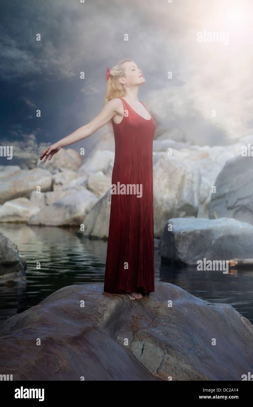 Una mujer en un vestido rojo está de pie sobre una roca en el agua y disfrutar del sol Imagen De Stock