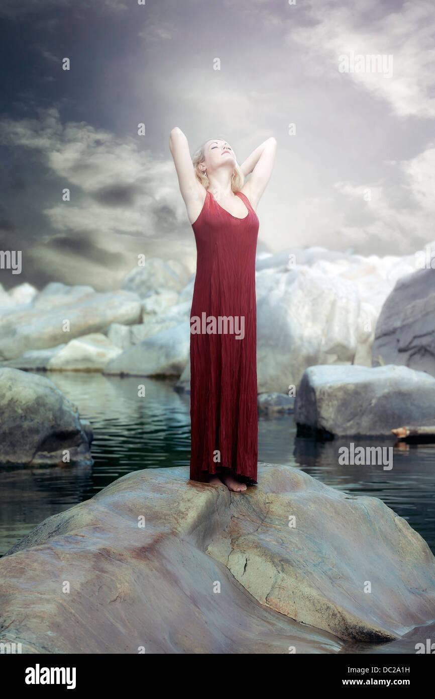 Una mujer en un vestido rojo está de pie sobre una roca en el agua y disfrutar del sol Foto de stock