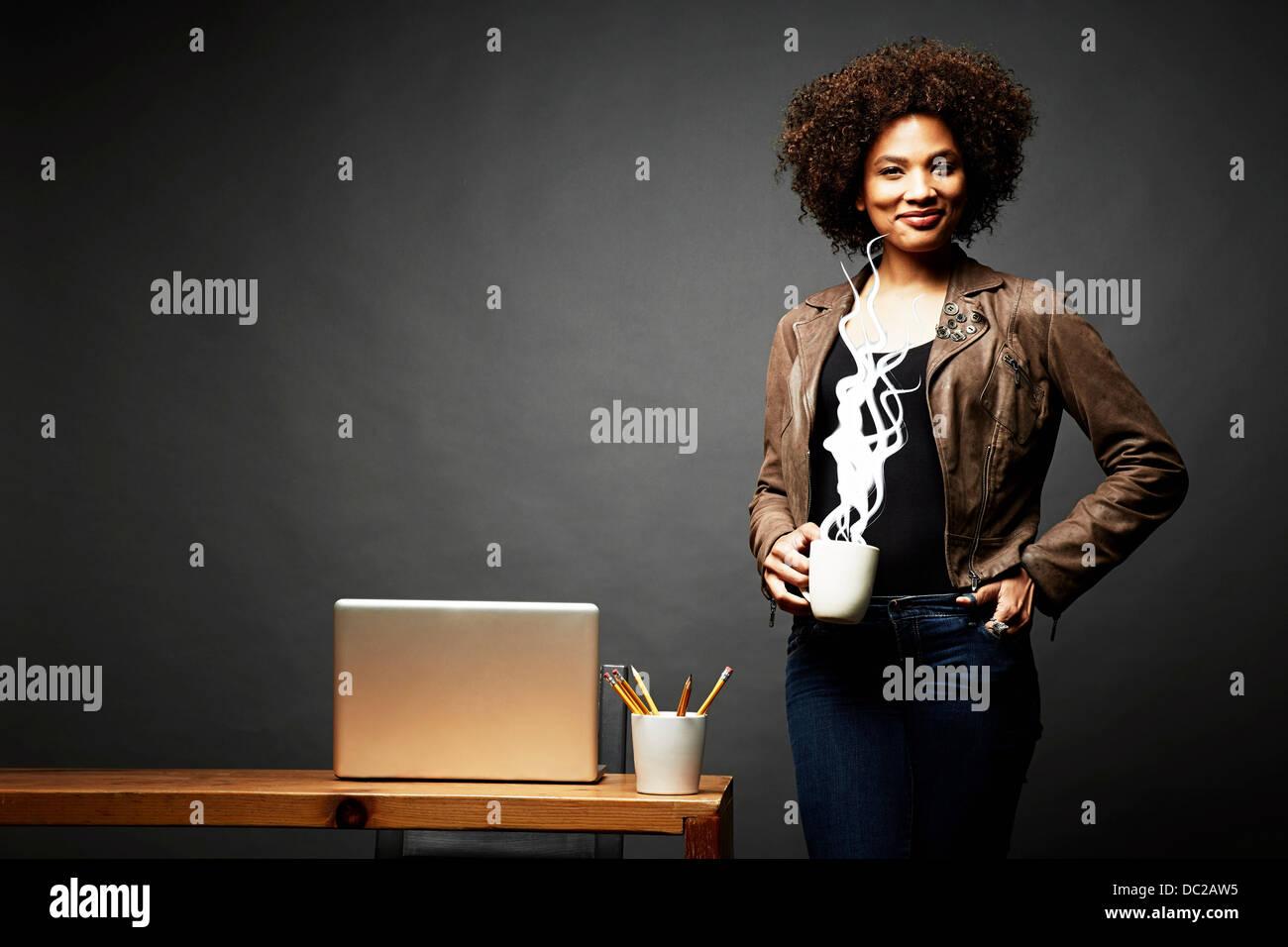 Mujer sosteniendo una taza de bebida caliente de vapor Imagen De Stock