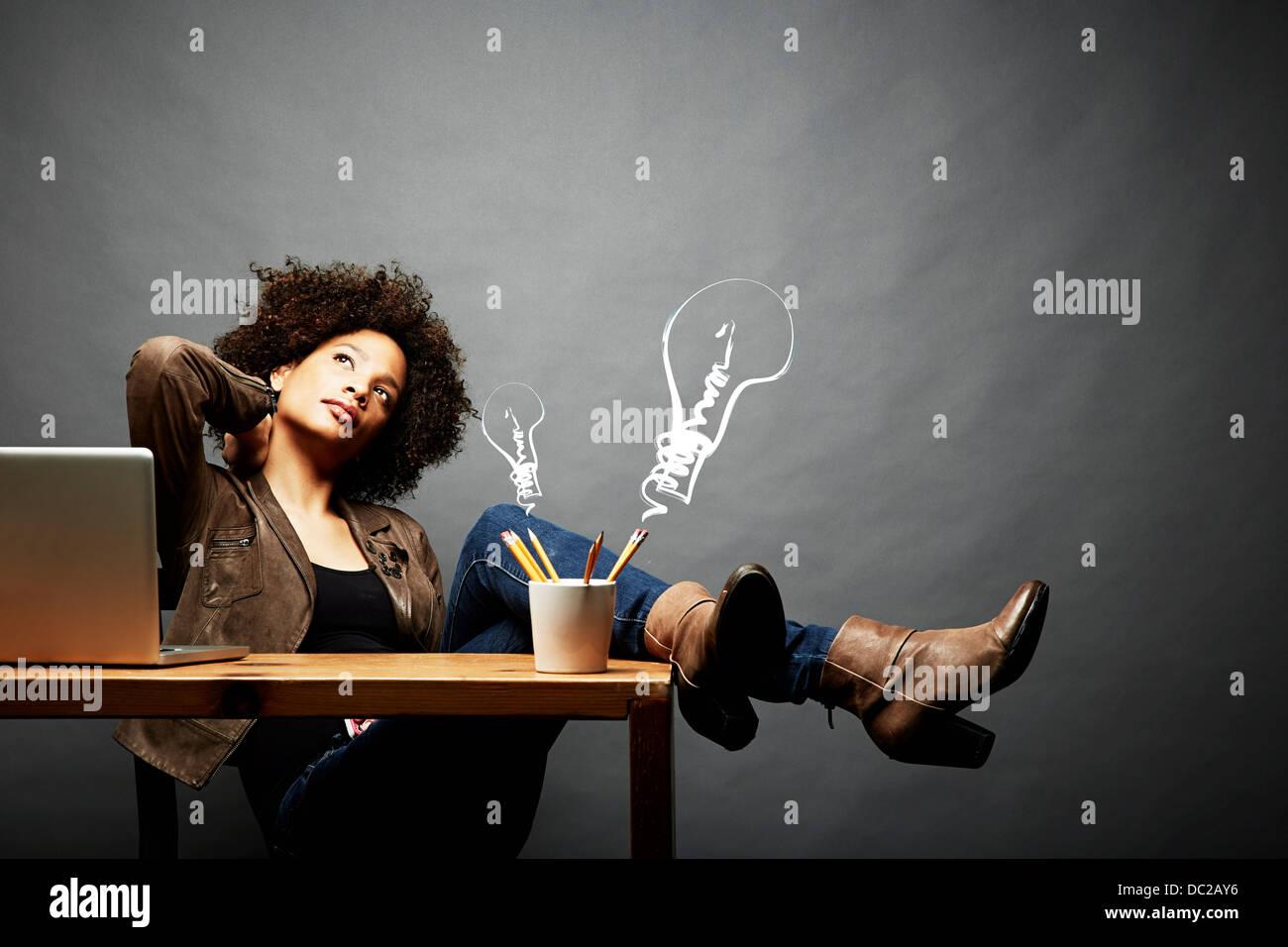 Mujer con las piernas sobre la mesa buscando ideas Imagen De Stock