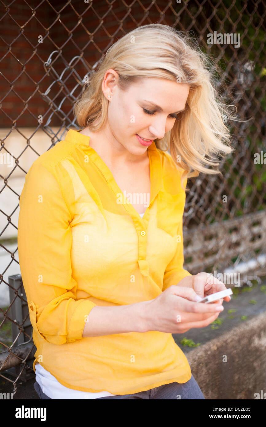 Mujer con teléfono móvil contra el eslabón de la cadena cerco Imagen De Stock