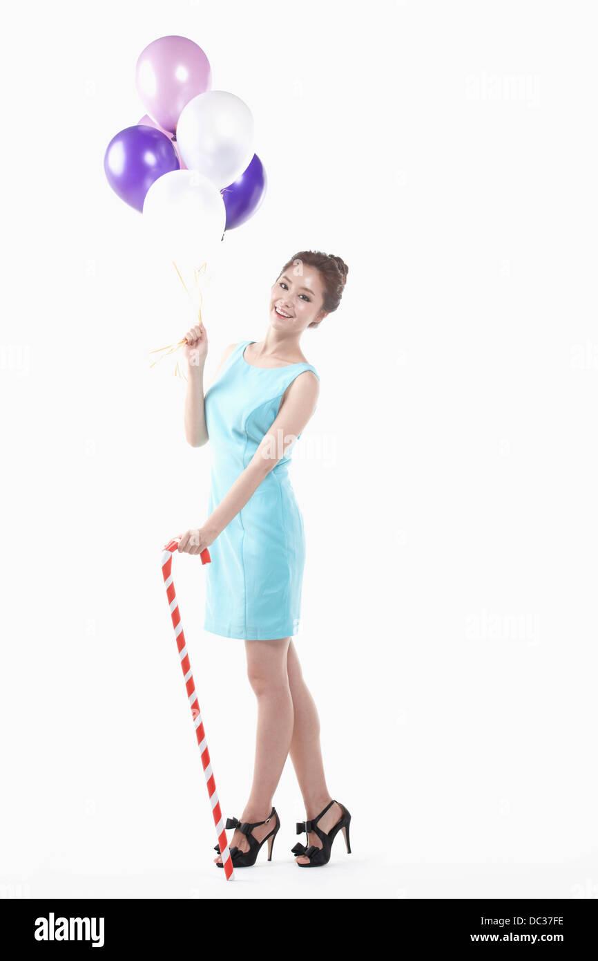 Una dama en mini vestido posando con globos y palo de caña Imagen De Stock