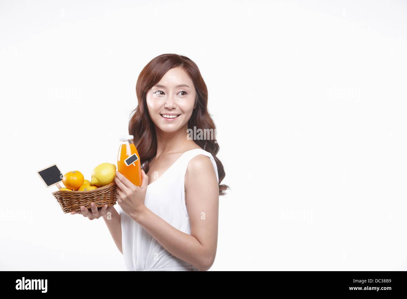 Una señora en vestido blanco sosteniendo una cesta de frutas y una botella de jugo Imagen De Stock