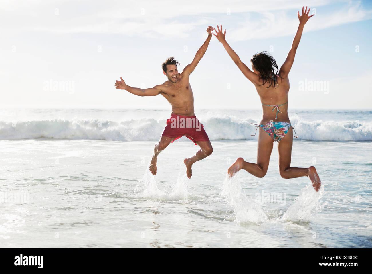 Par saltando con los brazos levantados en la playa Imagen De Stock