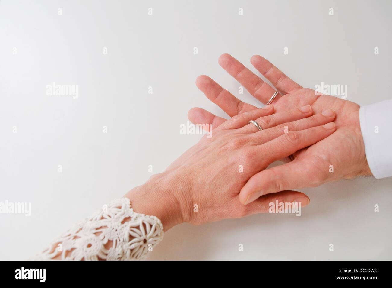 Pareja de manos usando anillos de boda. Imagen De Stock