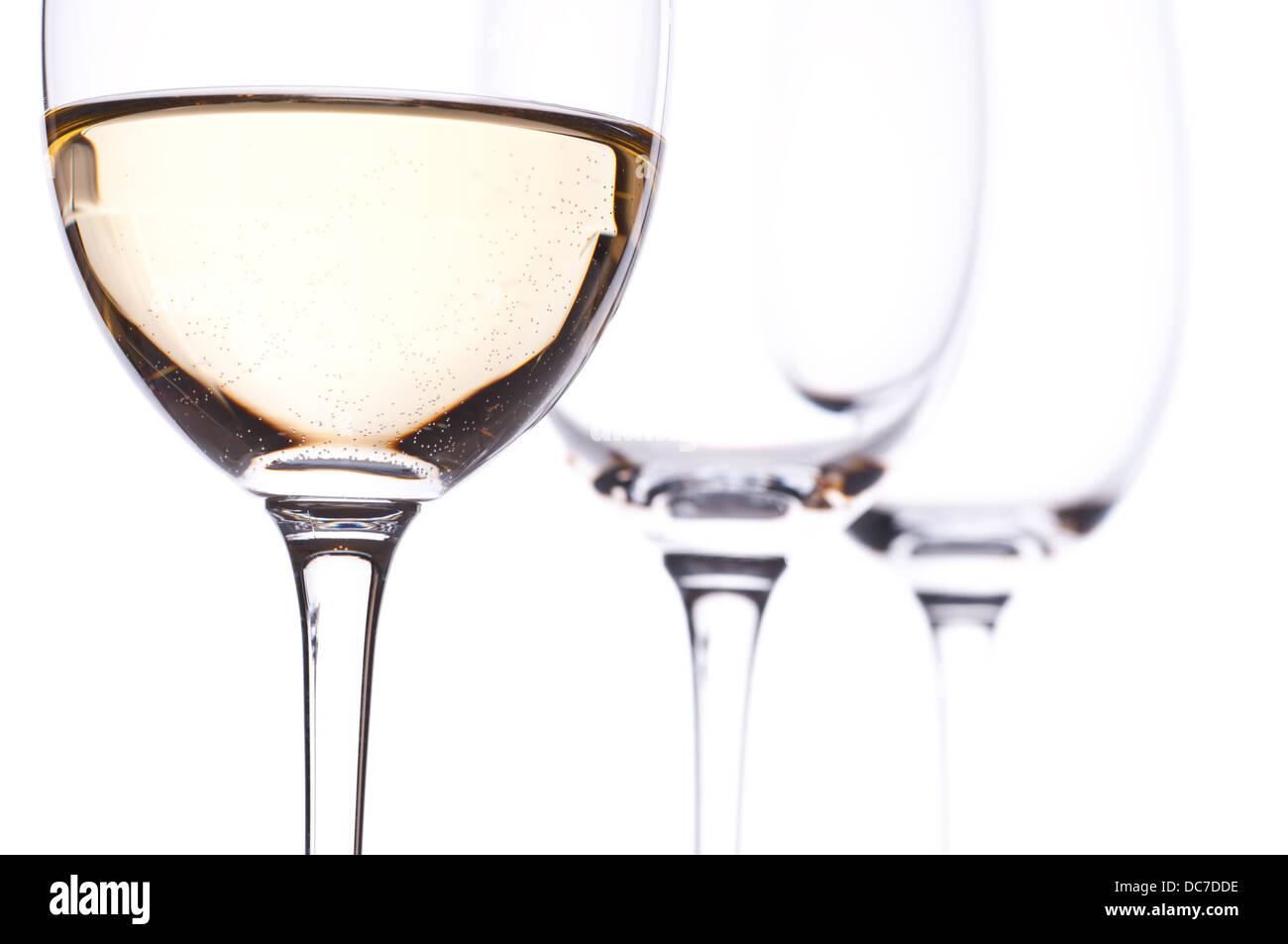 Tres vasos con vino blanco en la retroiluminación con fondo blanco. Imagen De Stock