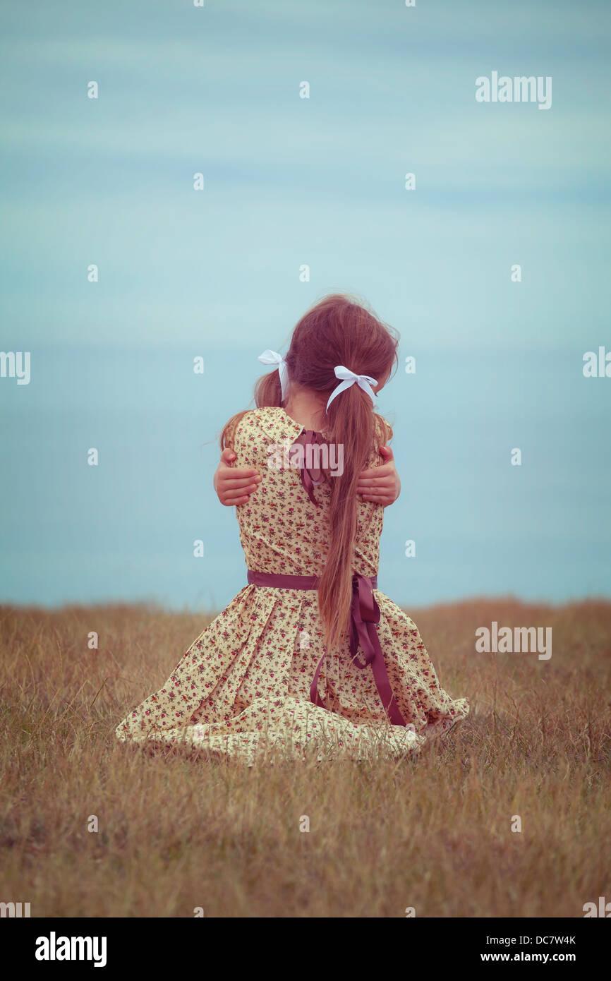 Una chica en VINTAGE DRESS, sentado en una pradera, abrazarse a sí misma Imagen De Stock