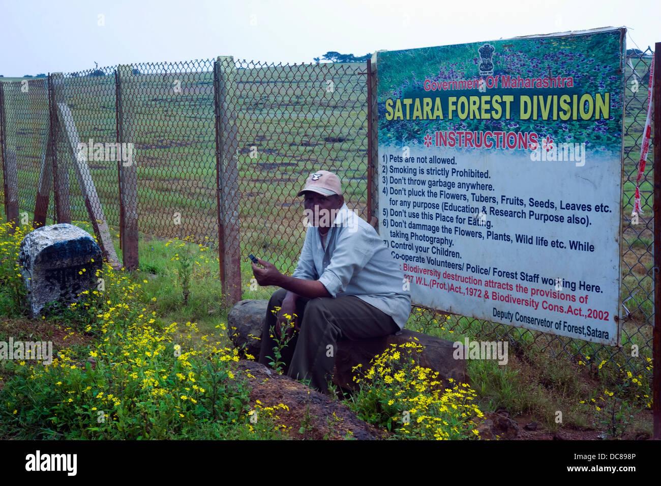 Guardia de seguridad sentado en frente de la División Forestal Cartel con instrucciones, Kass meseta, Satara Imagen De Stock