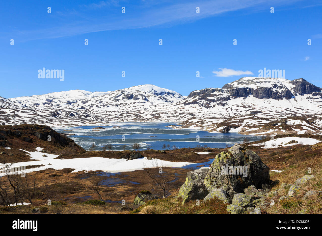 Lago Kjelavatn con nieve en las colinas y páramos de alta meseta a comienzos del verano. Hardanger, Telemark, Imagen De Stock