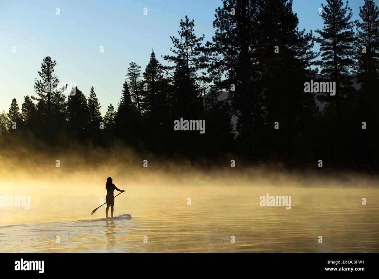Una mujer, , es silueteado Levántate Paddleboarding (SUP) al amanecer en la niebla en Lake Tahoe, CA. Imagen De Stock