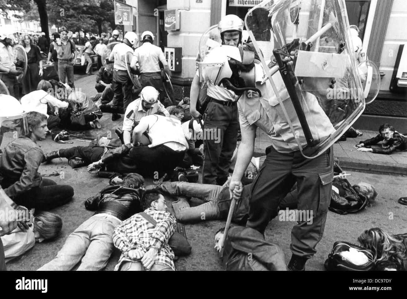 Policías y hombres de ambulancia en medio de manifestantes que yacía en el suelo y siendo parcialmente Imagen De Stock