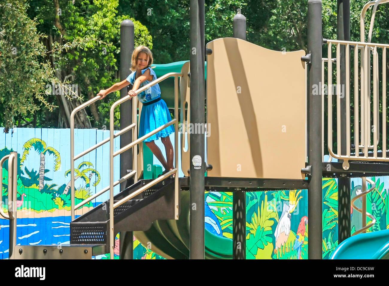 a20c44b54 Niña juega solo entre los columpios y toboganes en un parque en la Florida