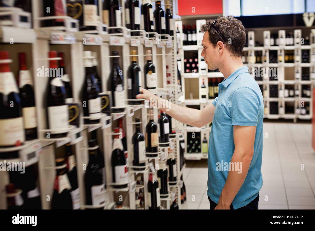 Elegir el vino en la tienda Imagen De Stock
