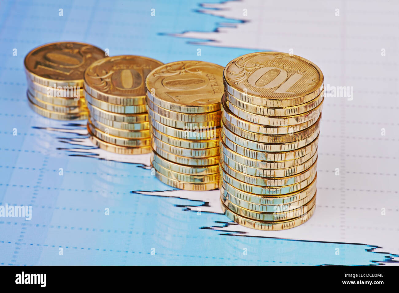Subida apila monedas,en los gráficos de cotizaciones financieras como fondo. Enfoque selectivo Foto de stock