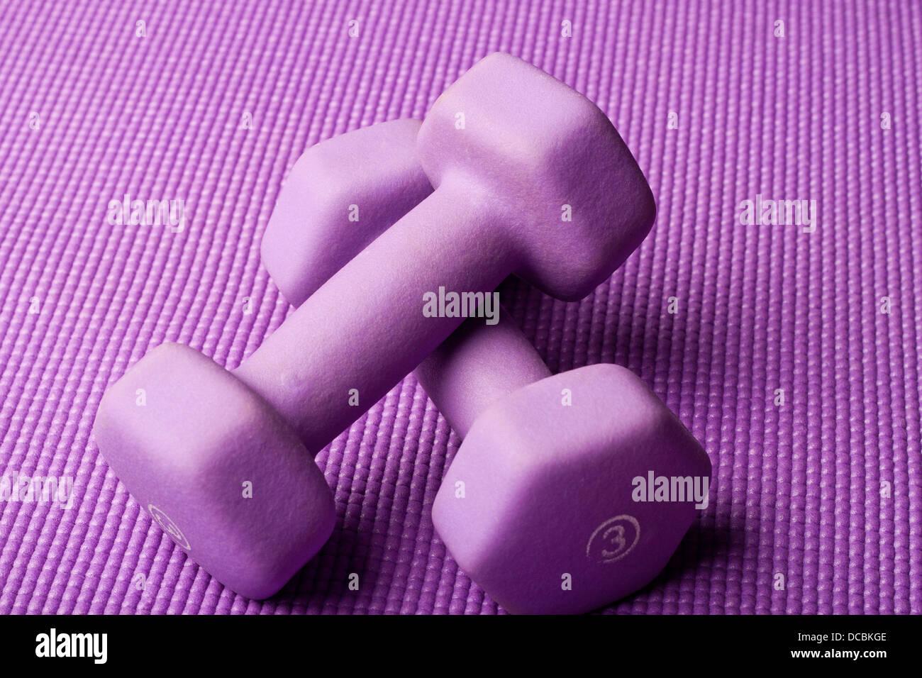 Violeta púrpura contrapesos en una estera del yoga Foto de stock