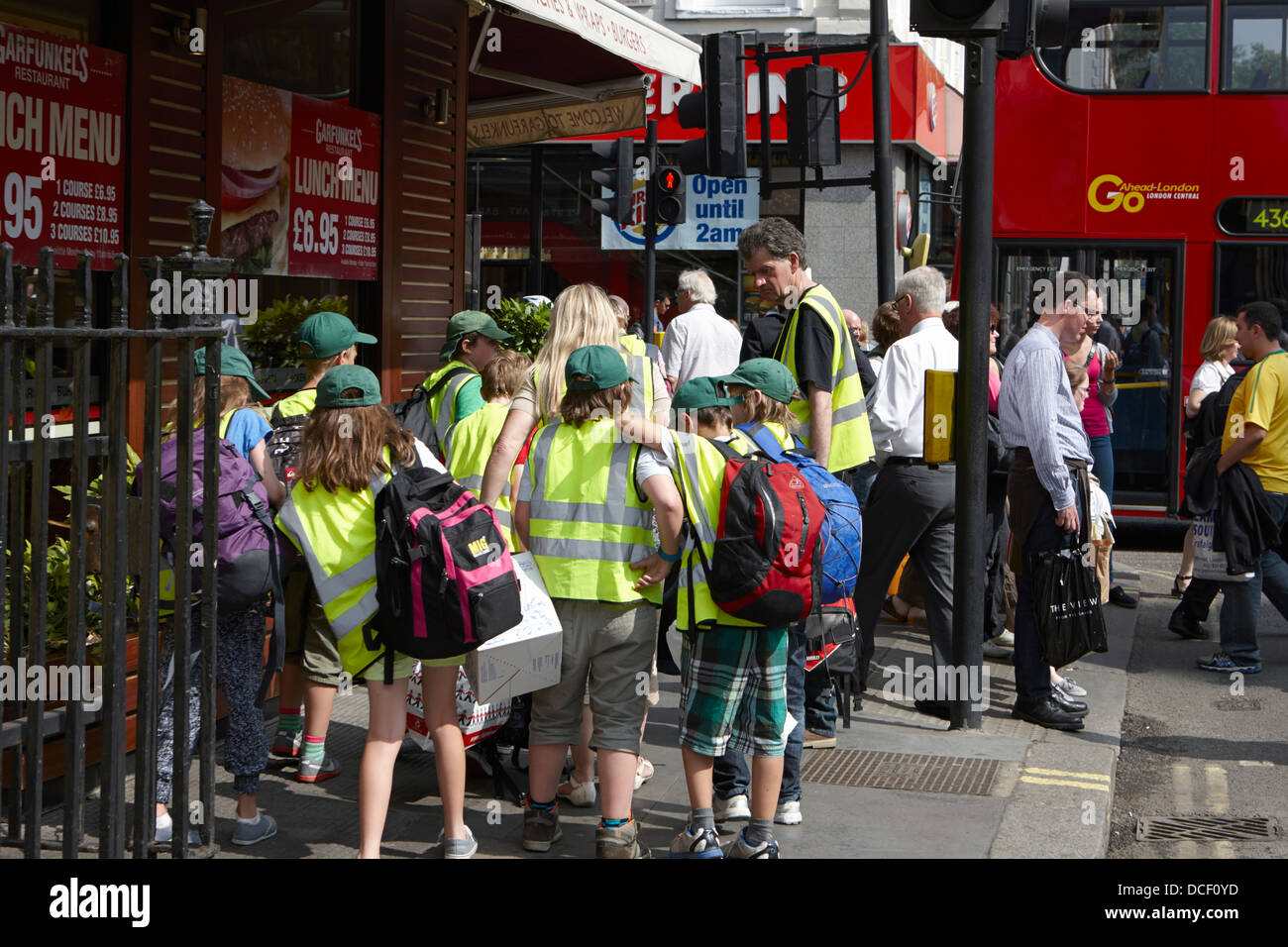 Los niños en la escuela de viaje a Londres vistiendo chalecos alta visibilidad Inglaterra Imagen De Stock