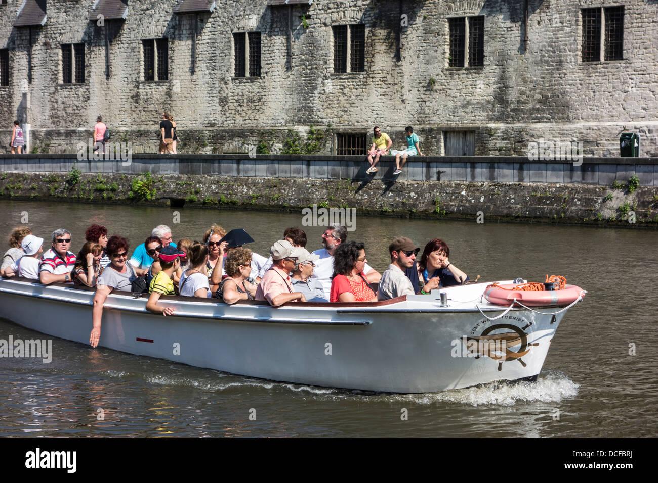 Los turistas en bote sobre el río Leie / Lys durante el viaje de turismo mirando el Groot Vleeshuis / Gran Imagen De Stock