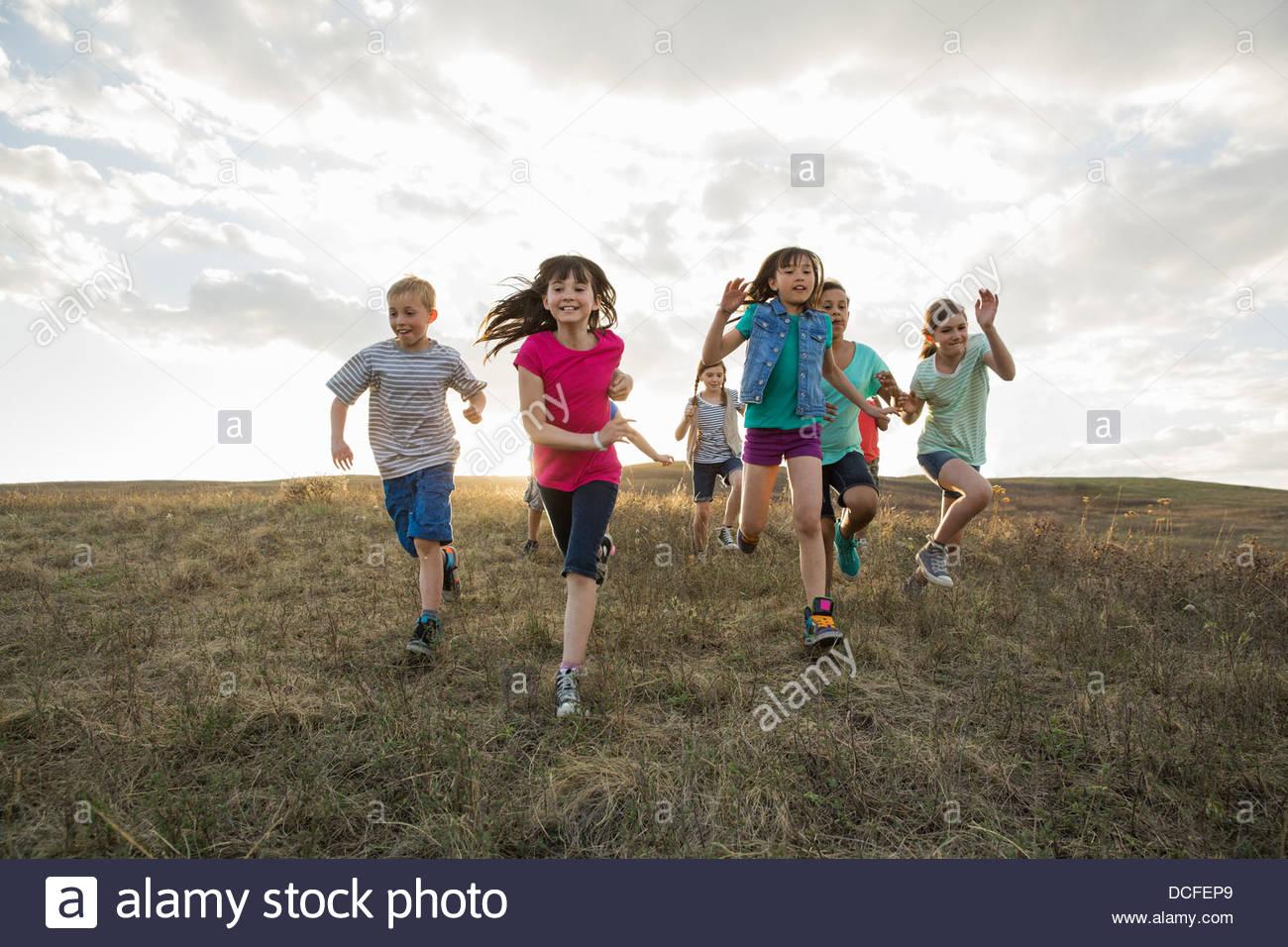 Excitados niños corriendo en Hillside Imagen De Stock