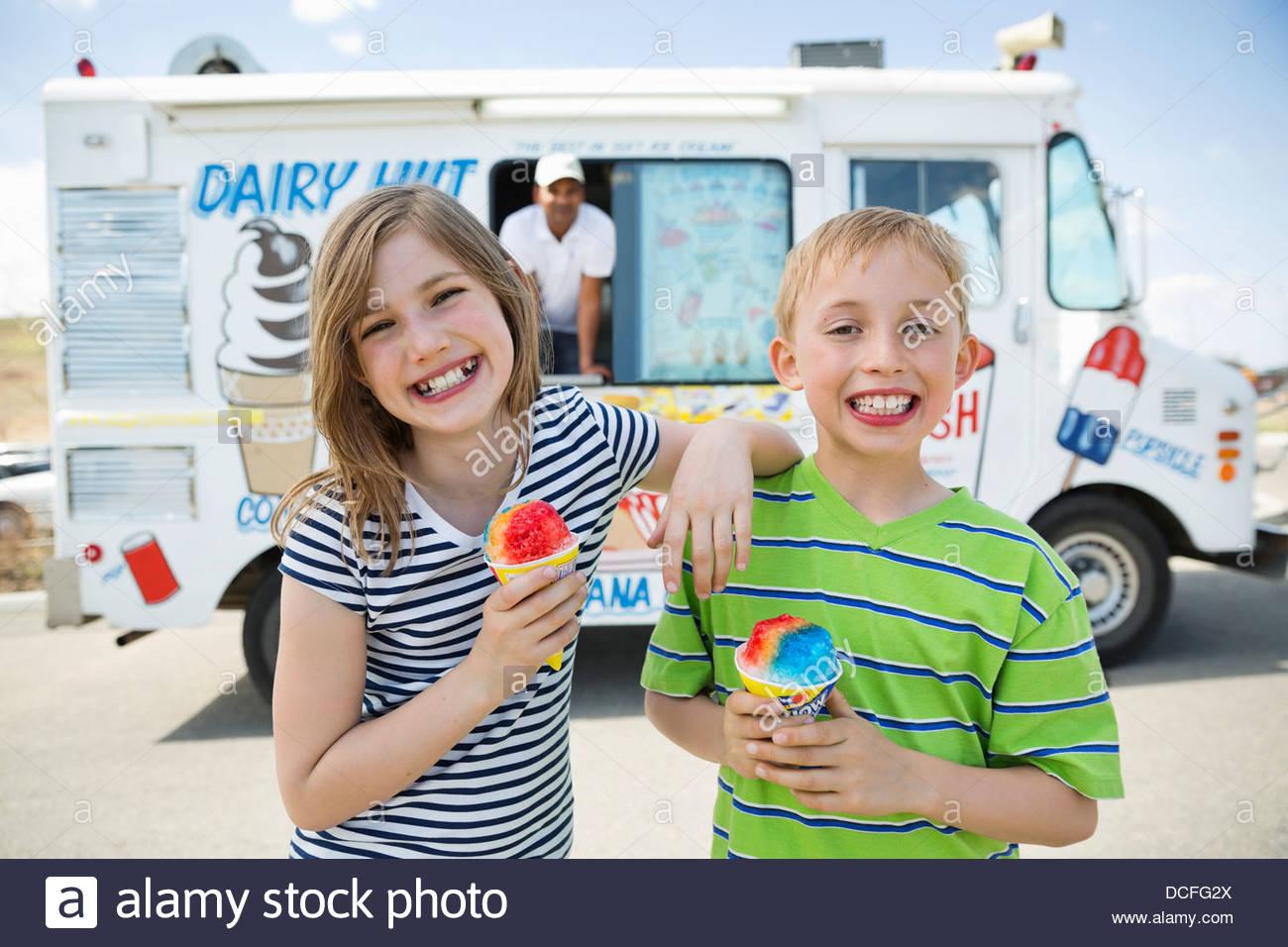 Amigos posando con los conos de nieve Imagen De Stock