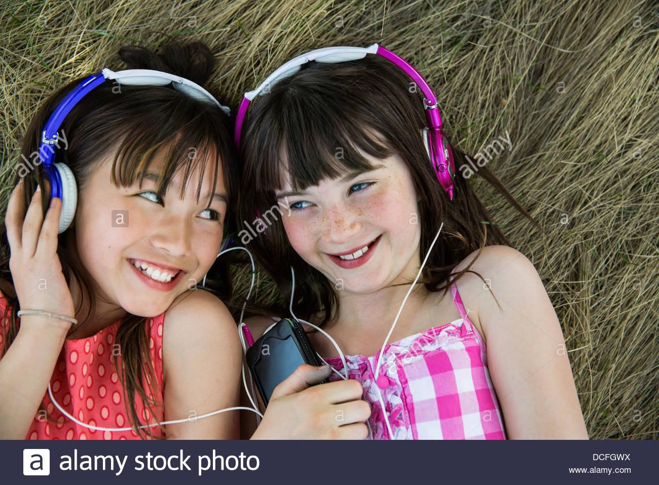 Las niñas acostado escuchando auriculares Imagen De Stock
