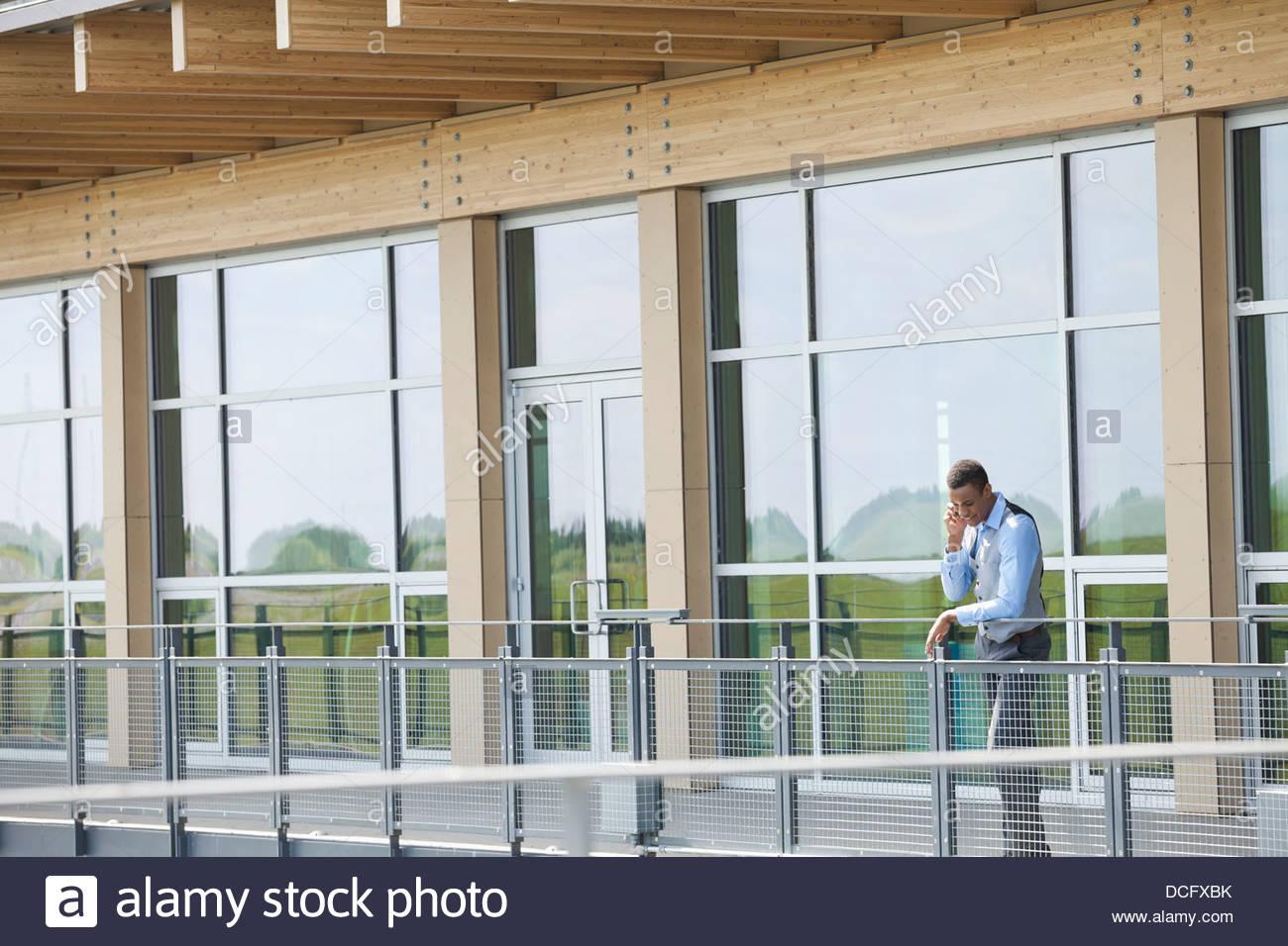 El empresario a través de teléfono móvil en el balcón Imagen De Stock