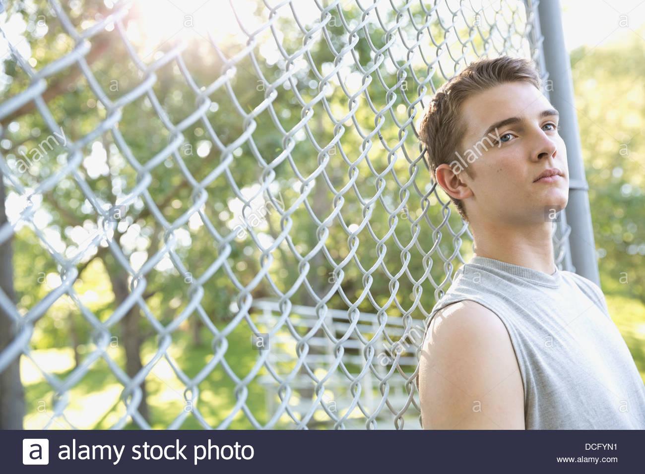 Pensativo adolescente recostada en cercado de cadenas Imagen De Stock