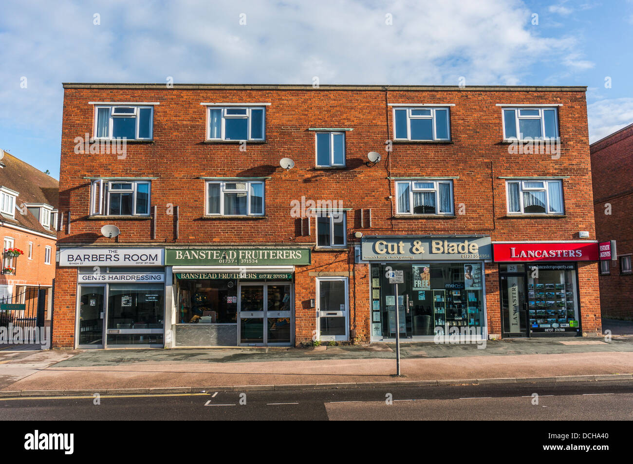 Bloque de tiendas locales independientes con pisos superiores, en Banstead Village High Street, en una tranquila mañana de domingo en Surrey, Inglaterra, Reino Unido. Foto de stock