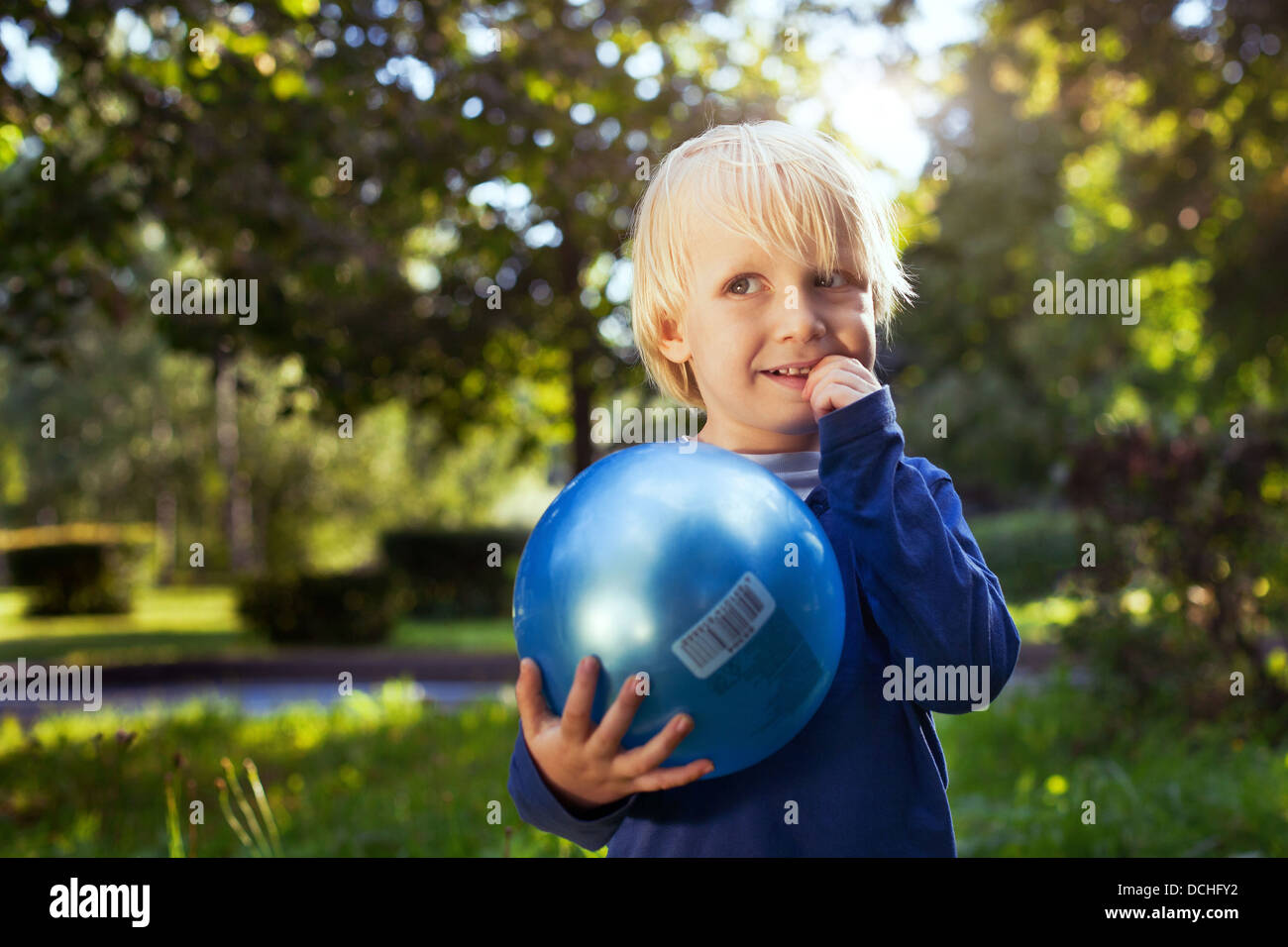 Poco chico lindo con el balón mirando hacia arriba Imagen De Stock