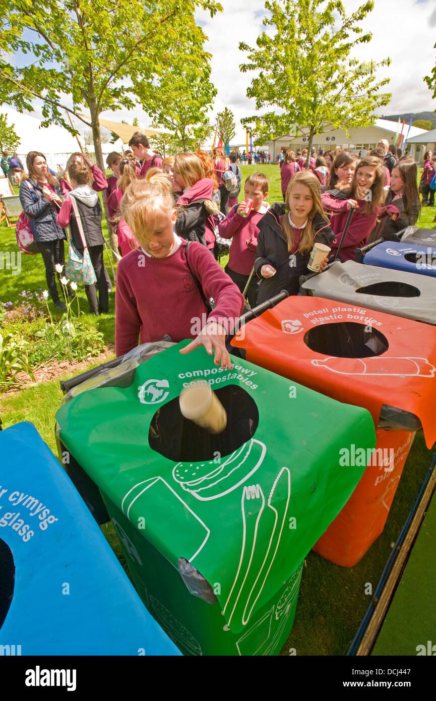Niños en edad escolar en el festival del heno colocar contenedores de residuos en una bandeja de reciclaje. Imagen De Stock