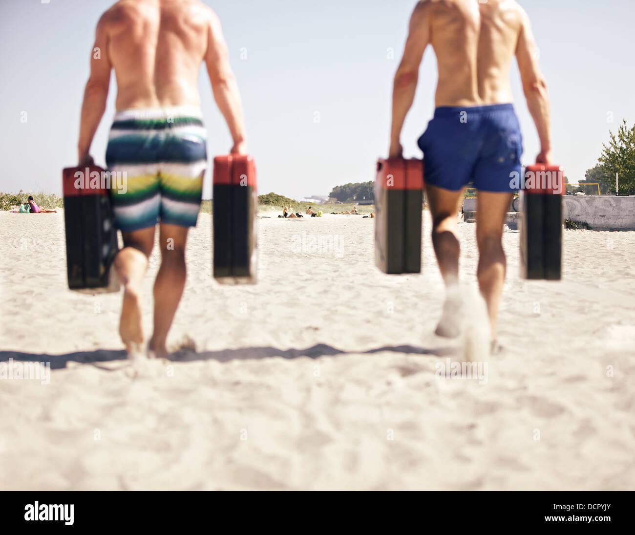 Dos hombres corriendo con bidones como parte de crossfit games Imagen De Stock