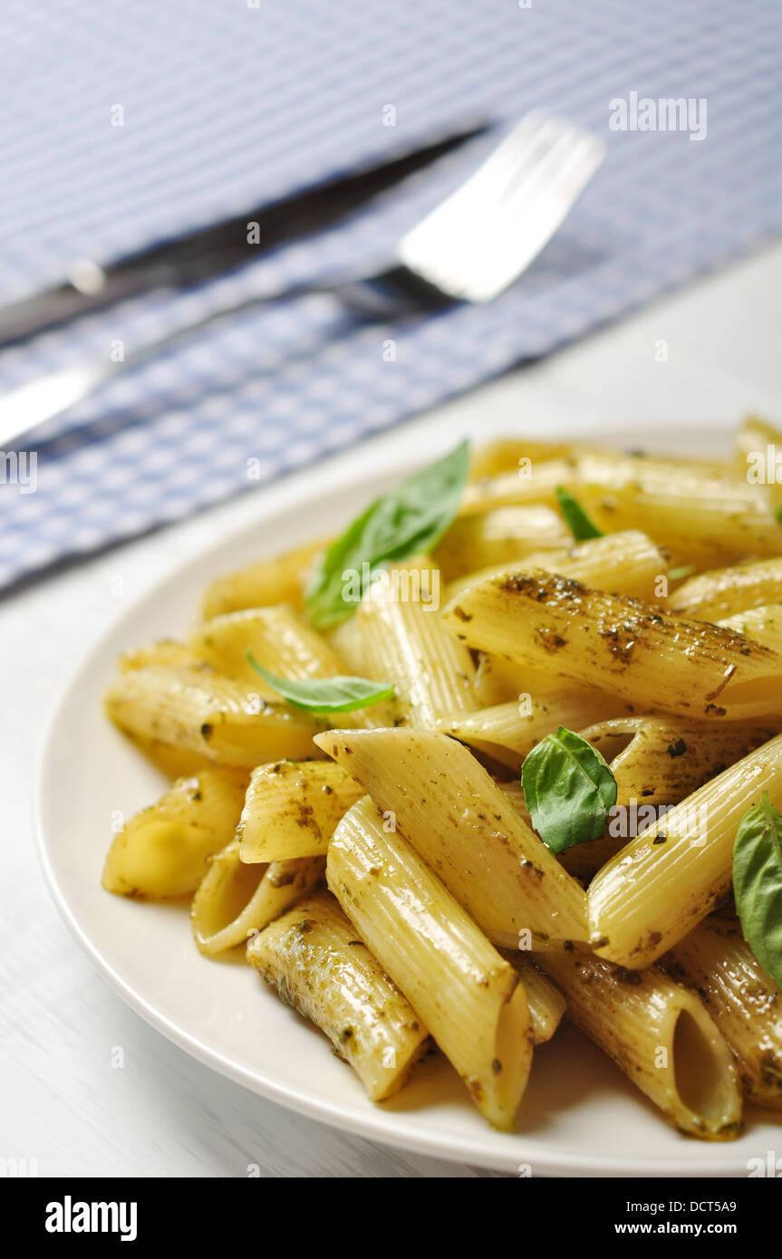 Penne pasta con salsa pesto y albahaca sobre placa blanca. Imagen De Stock