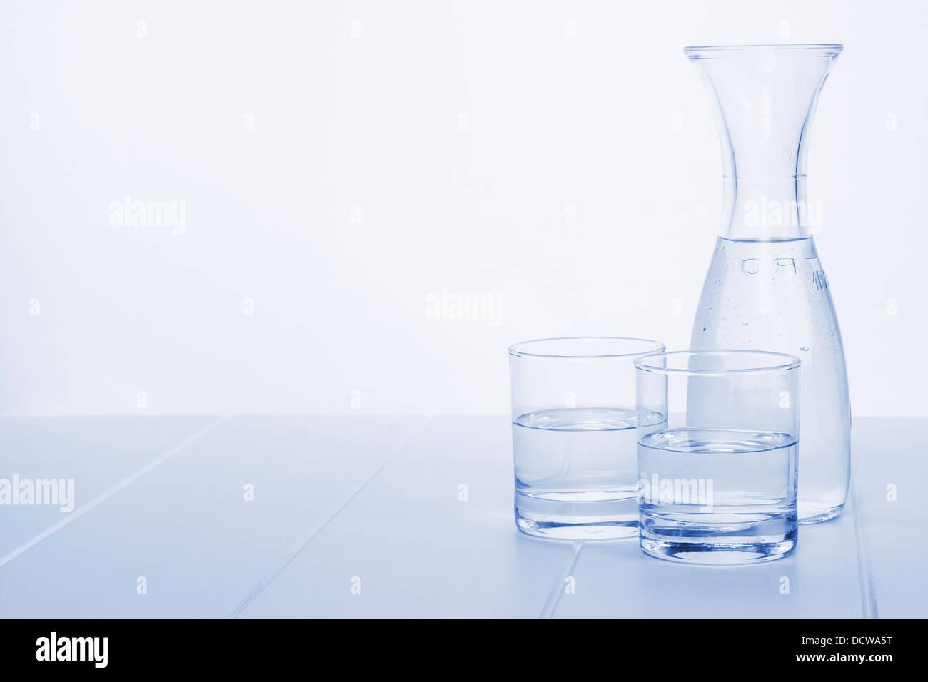 Garrafa de agua y dos copas: una garrafa de agua sobre una mesa con dos copas, en tonos de azul, horizontal. Imagen De Stock