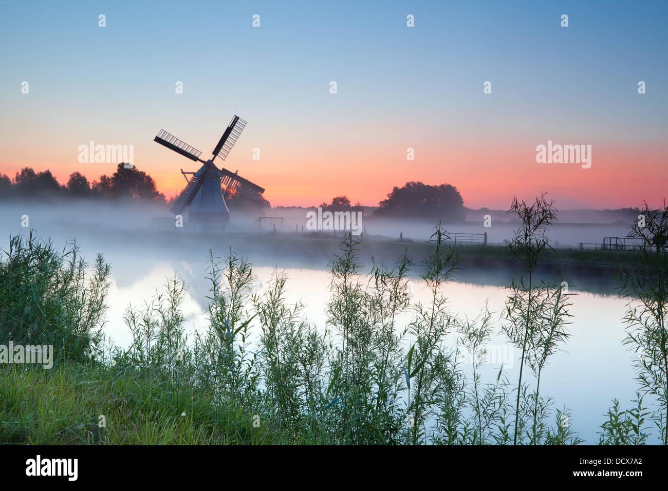 Molino Blanco holandés por río al amanecer, Groningen, Países Bajos Imagen De Stock