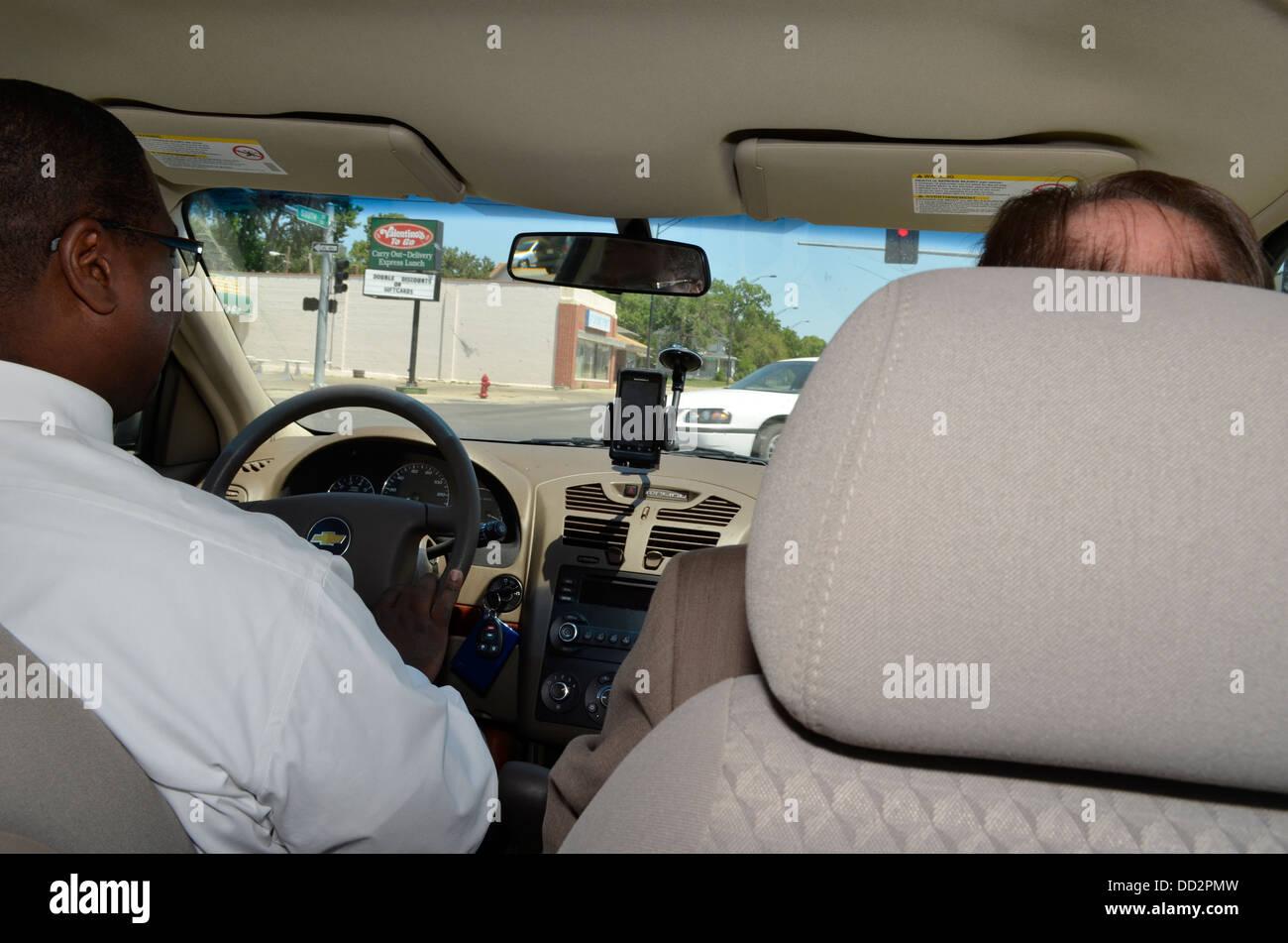 Dos varones de agentes de libertad condicional en el vehículo en su camino para satisfacer un parolee en su Imagen De Stock