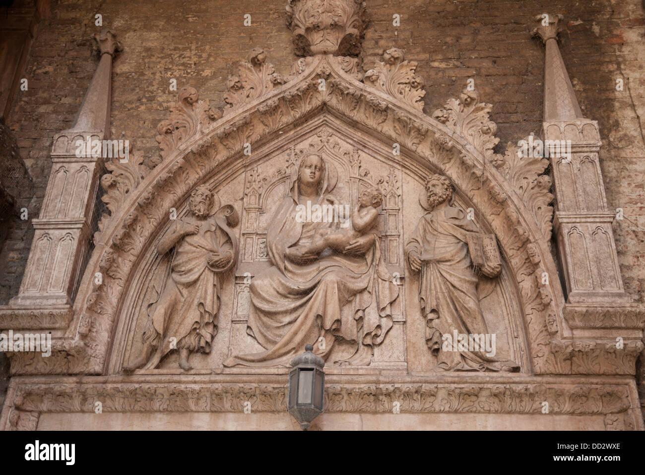 Una puerta de estilo gótico florido presentando Virgen María sosteniendo a Jesús, sat entronizada Imagen De Stock
