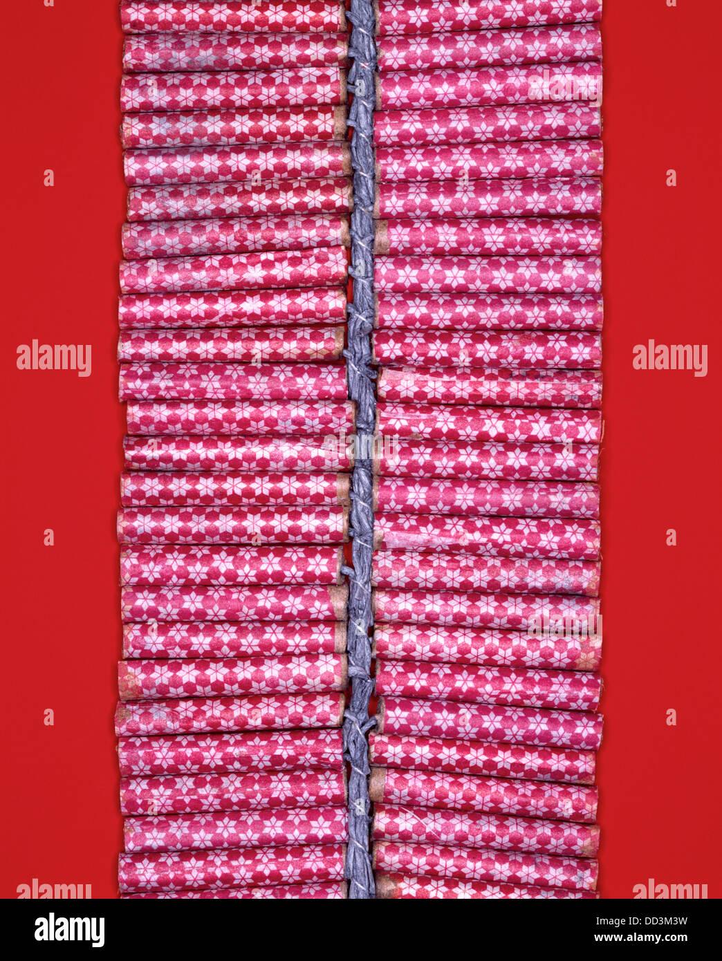 Una cadena de rojo petardos celebrada por un fusible. Fondo rojo brillante Imagen De Stock
