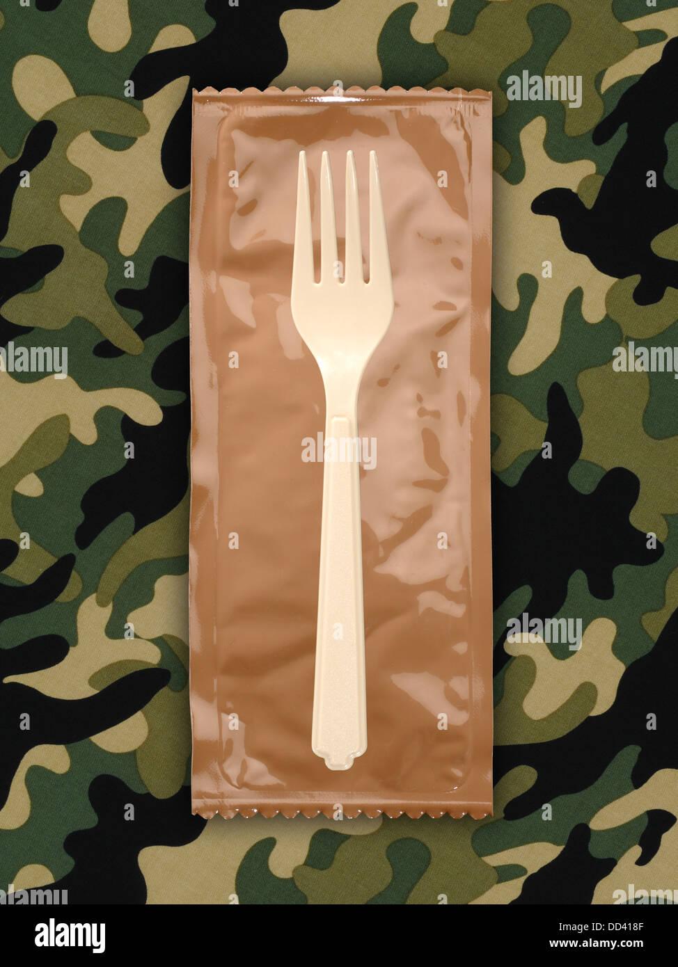 Raciones militares o MRE comidas listas para comer en un fondo camuflado. Los paquetes abiertos con utensilios de Imagen De Stock