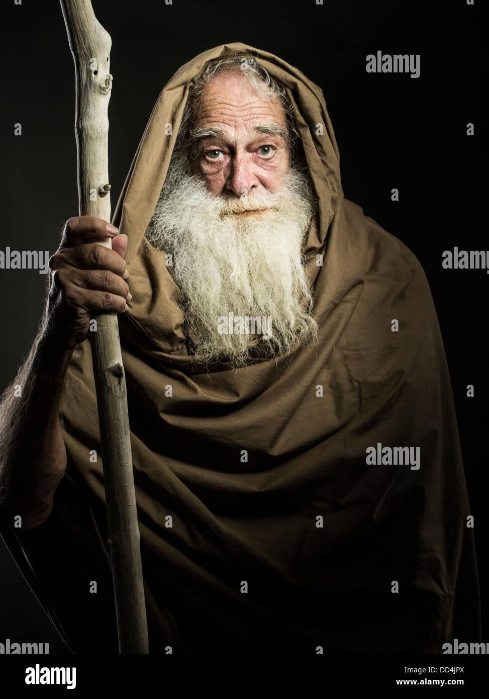 Hombre viejo con barba blanca y manto de personal parece asistente / Gandalf / Moisés / Dumbledore Foto de stock