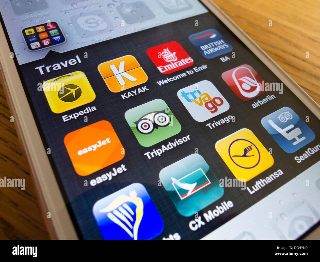 Detalle de muchas aplicaciones de viajes en un iPhone 5 teléfono inteligente. Imagen De Stock