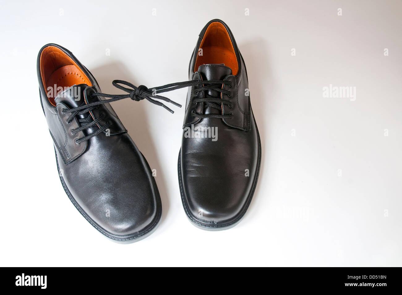 Par de zapatos con los cordones atados unos a otros. Foto de stock