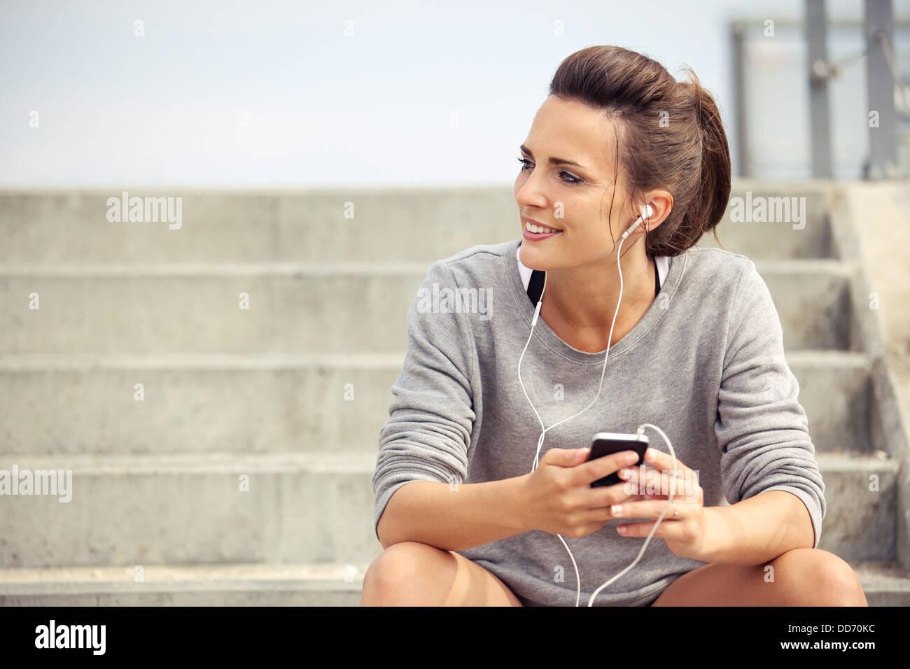 Feliz atleta atractivo sentarse y escuchar música mp3 mientras descansa Foto de stock