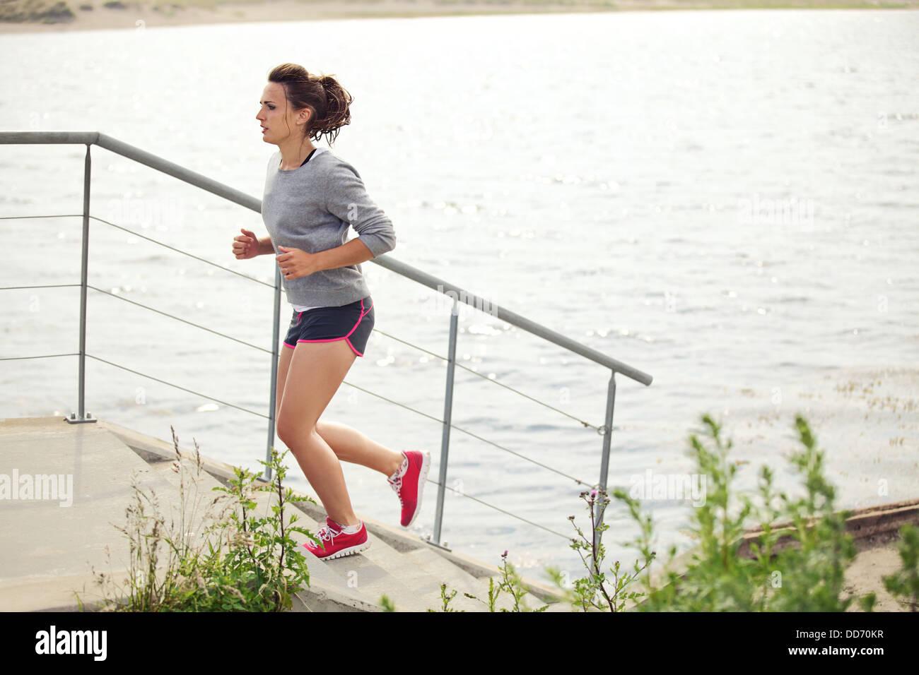 Joven atleta femenina haciendo ejecutando como capacitación y entrenamiento Imagen De Stock