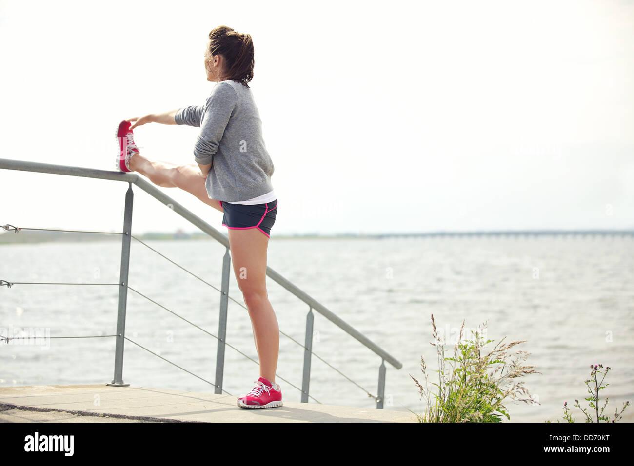 Participación activa de los jóvenes corredoras estirar sus piernas antes de ejecutar el ejercicio al aire Imagen De Stock